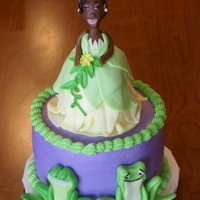 Princess And The Frog  Six inch round cake with rkt Princess Tiana on top. Fondant frogs on side of the cake. Matching cupcakes with fondant crowns and lily pads...