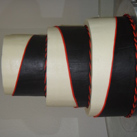 Black Wrap Cake 10in+8in+6in frosted in buttercream. Black fondant wrap with red fondant trim, and twisted fondant rope border.