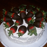 Chocolate Covered Strawberries Cake Chocolate covered strawberries on top of white cake with chocolate ganache filling.