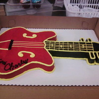 Red And Black Electric Guitar Cut and shaped from a half sheet of white cake, buttercream icing.