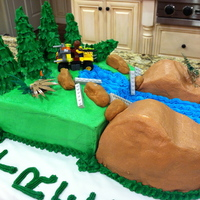 Lego Adventure Cake Large sheet cake, halved and stacked. Iced with green buttercream. One football shaped cake pan used to make large side rocks. I halved the...