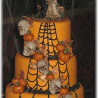 Halloween Wedding Cake Triple choclate cake with chocolate mocha buttercream covered in caramel marshmallow fondant. Decorations are fondant except the skulls.