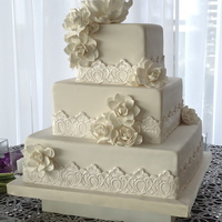 Gardenias & Lace Applique Three tier wedding cake covered in white fondant embellished with sugar flowers of gardenias and a peony on top. The lace applique made of...