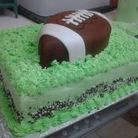 Football Cake   Chocolate fondant covered white cake football. White cake with oreo filling (marshmallow fluff recipe). Green b/c icing.