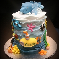 Nemo And Dolphin 2 tier vanilla cake, one with blue rainbow colours, other one all 7 layers of blue shades.