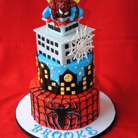 Spiderman Cake First two tiers are iced in buttercream. Top tier (the building) is covered in fondant. All accents are fondant, including the spiderman...