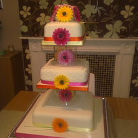 Gerbera Daisy Wedding Cake I made all of the gerbera daisy flowers by hand from sugar paste, and mounted the flowers inside the acrylic separators between the tiers....