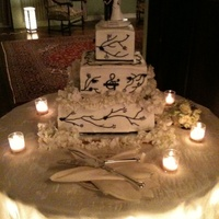 Black & White Cake is iced and piped with buttercream. Each tier is four filled layers. Bottom and top tiers are chocolate cake. Top tier is filled with...