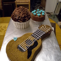 Acoustic Guitar   Buttercream and chocolate icing. Fondant pick. Tuning knobs are large chocolate chips.