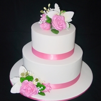 "Roses And Lilies 10"" dark chocolate mudcake bottom tier, top tier 7"" white citrus mudcake. All edible flowers, leaves etc."