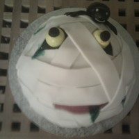 Halloween Mummy's Head With Spider Wilton Sports ball pan, with green butter cream and wrapped in rolled white icing.Gobstopper eyes and fondant spider.