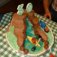 Kayak On The Waterfall Chocolate Brownie cakes tiered up to look like mountainous area covered in chocolate buttercream. The river was made with a marzipan base...