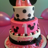 Minnie Mouse Cake Cake iced in buttercream with a pink fondant ruffle skirt at the bottom and black gumpaste ears at the top.