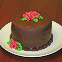 Chocolate Ganache Birthday Cake Cake is chocolate with raspberry ganache filling. The cake is also covered in raspberry ganache. The roses are made from fondant. TFL!