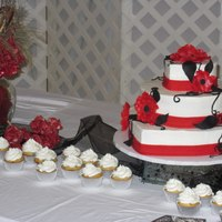 "Red, White, And Black!  Heart shaped tiers. Iced in white BC. Accented with red fondant band and flowers painted with luster dust; black fondant ""vines""..."