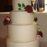 Tradional White Wedding 4 tier white fondant with gum paste roses and ranunculus in burgundy, raspberry, pinks & creams