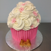 Big Cupcake Cake I made this one for my nieced birthday. The cake is iced in buttercream with fondant flowers and bow