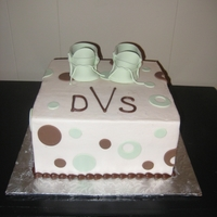 Baby Shower The cake is iced in buttercream with fondant polka dots and gumpaste baby booties.