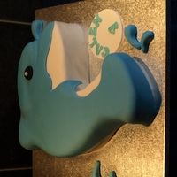 Dolphin Sponge cake hand carved into a dolphin shape and covered with fondant . Cupcakes to match also made