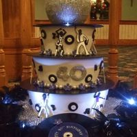 Disco   Tiered cake with the records and dancers made of gum paste. We also added lights.