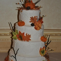 Fall Wedding Cake   Four tier round Autumn Wedding Cake with edible leaves, pumpkins and branches.