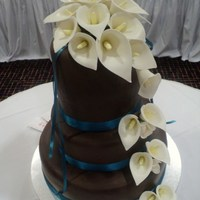 3 Tier With Sugarpaste Calla Lily's Double height 6 Inch dark chocolate mudcake top tier. 8 inch citrus mudcake middle tier. 12 inch marble mudcake bottom tier. All covered...