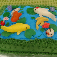 Koi Pond Cake Chocolate and vanilla cake, chocolate pudding filling. Buttercream frosting with fondant koi fish and lilly pads.