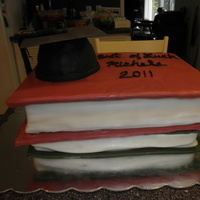 Graduation To A New World. Yellow cake filled with chocolat pudding. Books are thin cardboard with fondant. The cap is made of rice treats, morter board is fondant...
