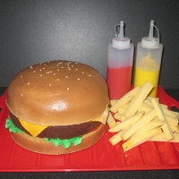 "Hamburger And Fries The hamburger bun is a 8"" vanilla cake iced with buttercream and airbrused. the meat is a 8"" chocolate cake. lettuce, tomato and..."