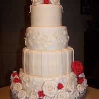 Ivory Roses Wedding Cake Ivory wedding cake with roses. Customer wanted a few red accents since it is Christmas time. Was a fun cake to make!