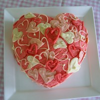 Pink Heart Cake Vanilla cake covered in buttercream and white chocolate piped hearts.