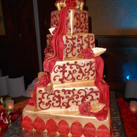 Red And Gold Indian cake. Airbrushed gold, red roses and draping, gold leaves. couple provided the elephants on top