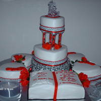 1320256360.jpg Red, White, Black Wedding Cake. 9 Different cakes in heart shapes and open book. Used Sugar Sheets for the Black and white trim.