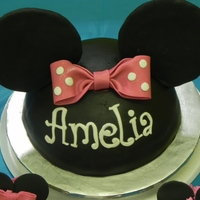 Minnie Mouse Cake Chocolate minnie mouse cake covered in chocolate fondant. All fondant details. Made cupcakes to match.