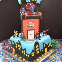 "Super Hero Birthday Cake 10"" by 10"" square cake covered in fondant. The building is a dummy cake and the figurines are toys. The customer brought me a..."