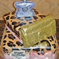 Fashionista Fondant painted with leopard spots with Michael Kors purse and NYC no. 9 perfume bottle made from rice crispies and fondant.