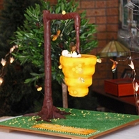 Suspended Bee Hive Christening Cake A beehive suspended in a tree over green grass with yellow flowers. Baby bee sleepinn on top with bee friend flying around him.
