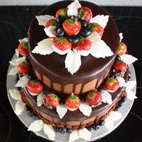 Chocolate Cake Chocolate cake, vanilla-oreo mousse filling, chocolate frosting and poured ganache. Fresh dipped strawberries and blueberries. White...
