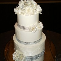 White And Silver Valentines Wedding Cake Three tiered wedding cake for a valentines day wedding. Hand made flowers, buttercream iced. All vanilla cake with SMBC filling.