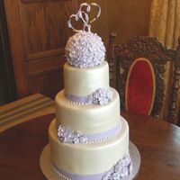 Simple Lavender And Ivory Wedding Cake The bride saw a cake in a Wilton book and really liked the flowers (piped royal icing) but wanted the cake to look different. She wanted a...