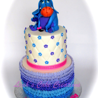 "Sweet Eeyore Buttercream ruffles on the bottom tier, Eeyore made from rice krispy and modeling chocolate. 7"",5"" rounds."