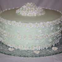Apple Blossom Flowers 10 inch round cake iced in buttercream, decorated with buttercream and royal icing flowers. Design inspired by Wilton.