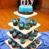 "It's A Boy!! 6 Inch topper with a cascade of cc decorated with ""onsies"" brown and blue to match invitations."
