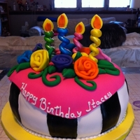 Neon Birthday Cake Black and white stripes covered with bright pink fondant. Flowers, leaves and candles are all made of fondant also.