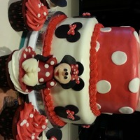 Minnie Mouse Theme Cake With Matching Cupcakes. two tier cake decorated in fondant.matvching cupcakes. main cupcake decoration made of modeling chocolate