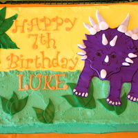 Dinosaur Cake   Sheet Cake made for 8 year old boy who had a Dinosaur themed party. I recreated the dinosaur that was on the invitations.