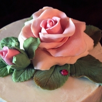 "Rose White Chocolate Cake Four layer 6"" dark chocolate cake covered with white chocolate. The topper is made entirely with white modeling chocolate. The bottom..."
