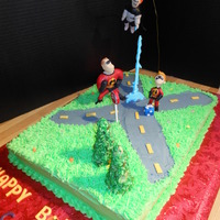 The Incredibles young boy requested buttercream cake with grass and a road with figures.
