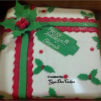 Christmas Present Gift box cake covered in fondant topped with holly's cut with a cricut cake machine. The label was also cut with cricut.
