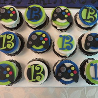 Video Game Cupcakes! Chocolate cupcakes with vanilla icing to go with the PS3 cake for my grandson's 13th birthday! Toppers are made of fondant! I printed...